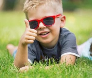 A boy lying on the green grass wearing red sun glasses
