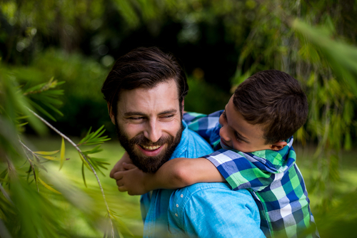 father and son enjoying outdoor in a pest free lawn after pest control service in Oklahoma